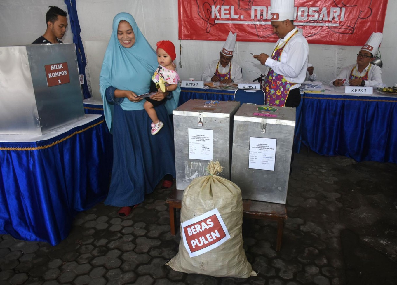 Polling station officials in Mejosari subdistrict, Malang municipality, East Java, are wearing aprons and chef's hats at the kitchen-themed polling station. Most of the officials work as cooks on Wednesday, June 27, 2018. JP/Aman Rochman