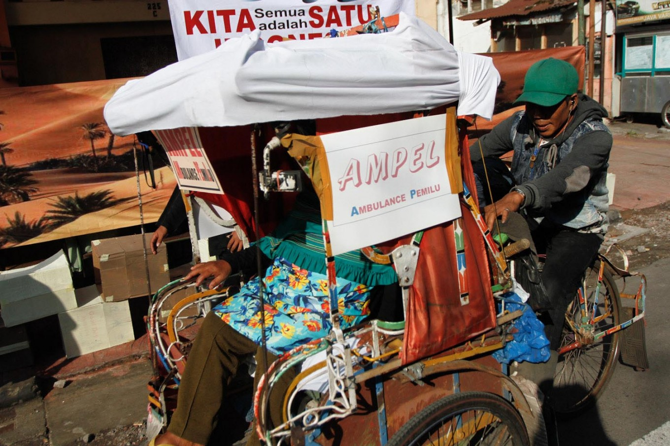 An official drives a voter back home in a pedicab after she cast her vote in Cibadak subdistrict, Astana Anyar district, Bandung on Wednesday, June 27, 2018. The neighborhood unit officials in the subdistrict hired pedicab drivers to pick up and take home elderly voters so they could cast their votes. JP/Arya Dipa