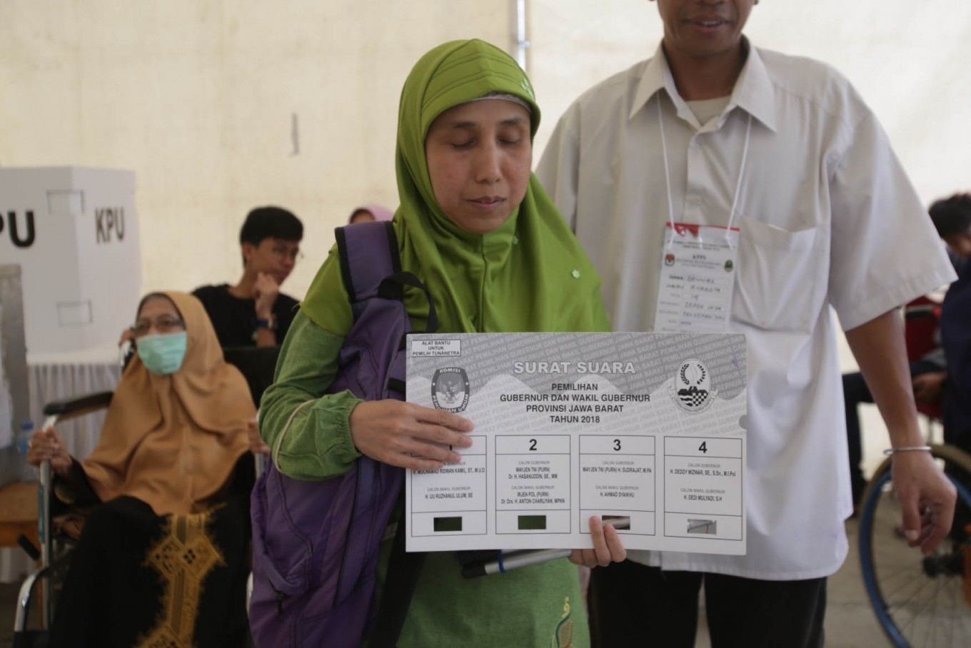 A disabled woman casts her vote in the West Java gubernatorial election at a carnival-themed polling station in Pondok Jaya, Depok, West Java on Wednesday, June 27, 2018. JP/Wendra Ajistyatama