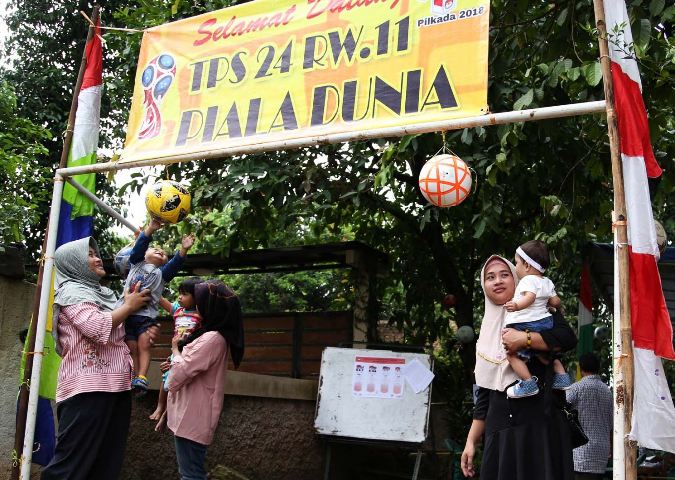Three young mothers hold their babies at the entrance to a World Cup-themed polling station in Tapos, Depok, West Java. on Wednesday, June 27, 2018. JP/P.J. Leo