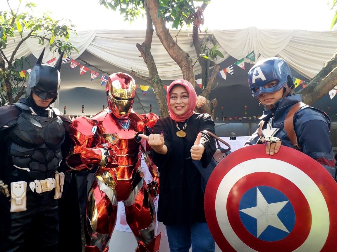 """A voter poses with """"Batman"""", """"Iron Man"""" and """"Captain America"""" after casting her vote in the West Java gubernatorial election in Citarum district, Bandung, West Java on Wednesday, June 27, 2018.  JP/Dewi Yulianti"""