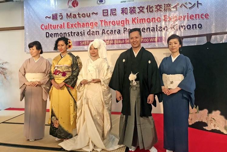 Iconic attire: Yuko Nakano (far right) and Miyuki Ishii (far left) pose with three matou (kimono demonstration) participants who are wearing a long-sleeved furisode (second left), a hanayome kimono for brides (center) and a male kimono, montsuki hakama.