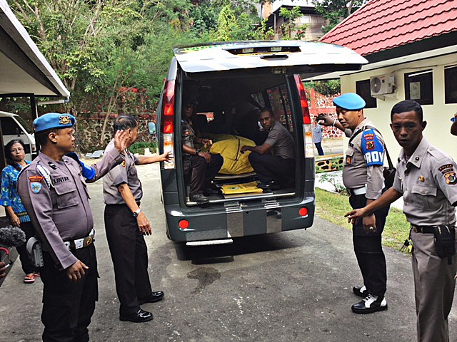 Fatal attack: Personnel remove the body of Brig. Sinton Kbarek from a vehicle for an autopsy at Bhayangkara Hospital in Jayapura, Papua. Sinton's body was found four days after he was reported missing on June 27. Sinton was buried in Jayapura on July 3.