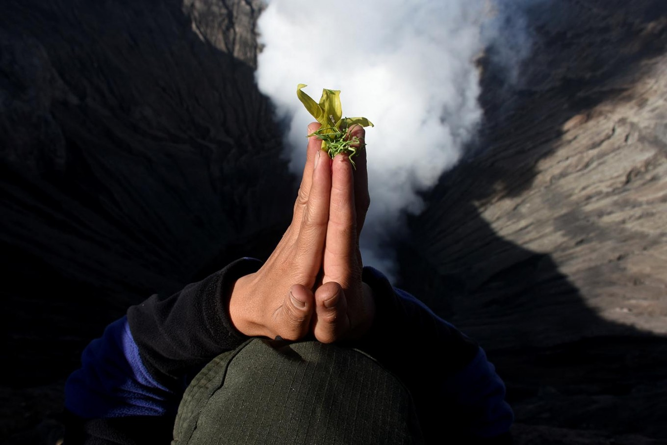 Don't look down: A member of the Tengger tribe prays over the crater of Mount Bromo. JP/ Aman Rochman