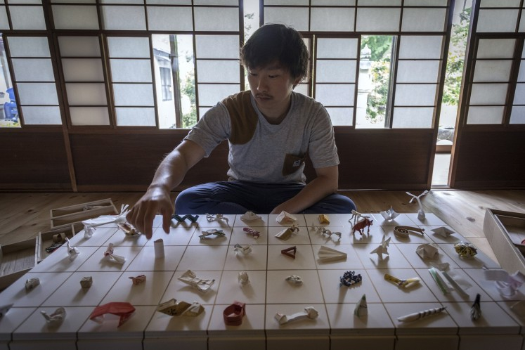 In this picture taken on May 23, 2018, Yuki Tatsumi sits next to his collection of origami made from chopstick sleeves in Kameoka, Kyoto prefecture.