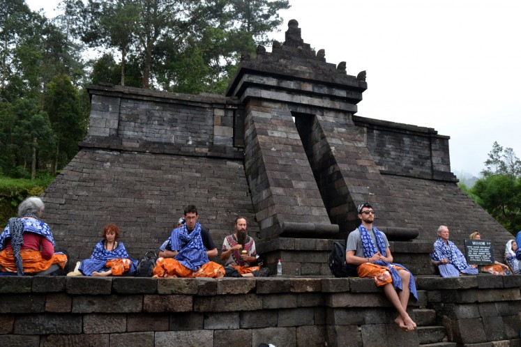 Foreign visitors studying Javanese spiritualism meditate at Cetho Temple in Central Java.