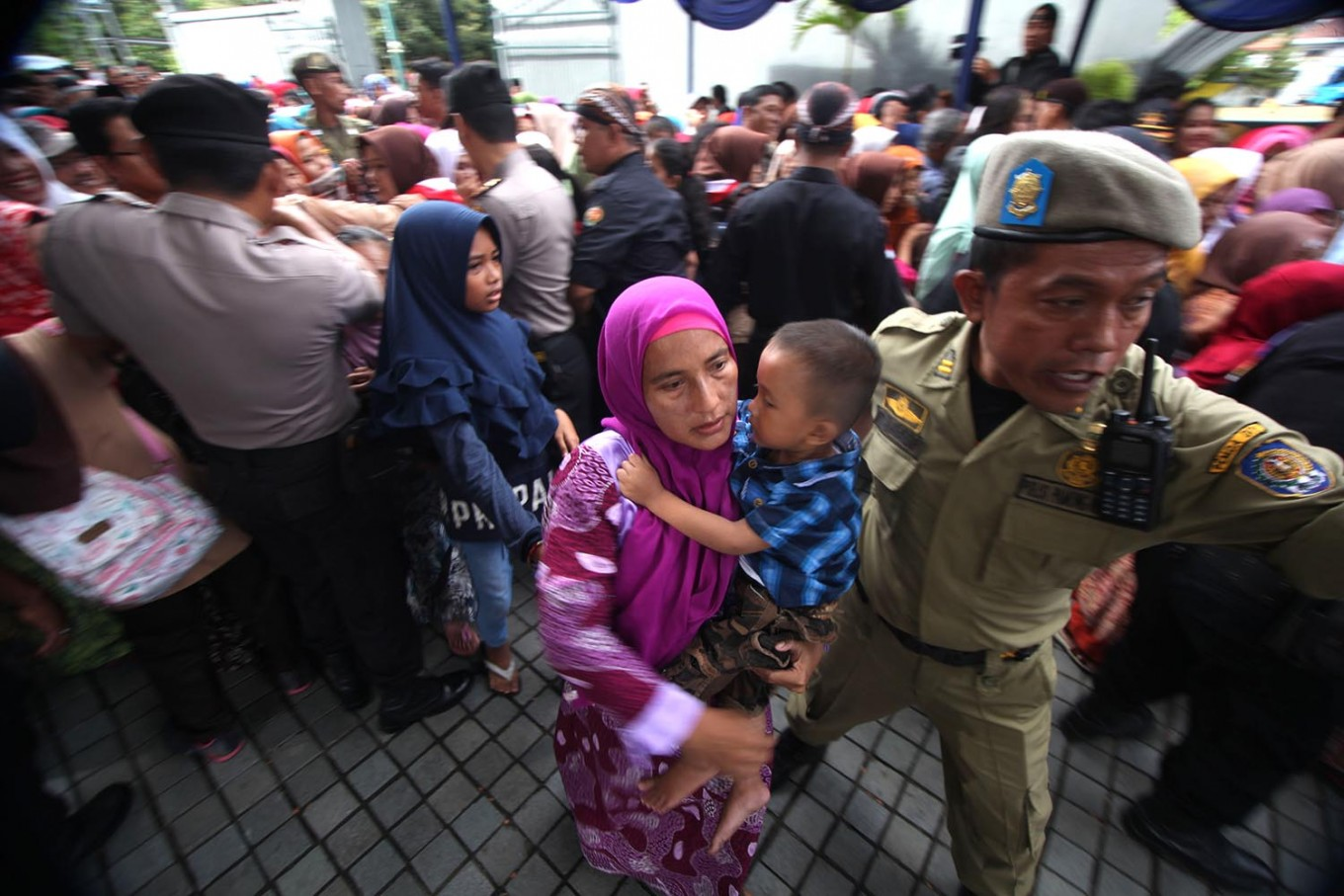 A public order officer escorts a mother and son to a safer place after being squeezed in the line. JP/Boy T. Harjanto