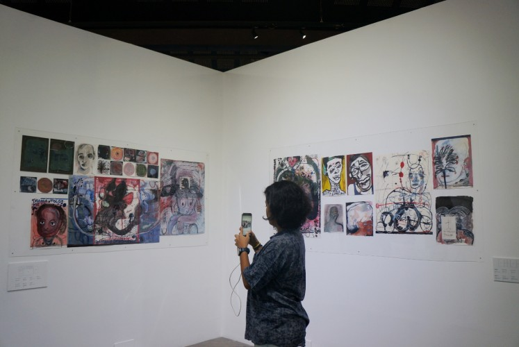 A visitor takes a photo of artist Natisa Jones' work.