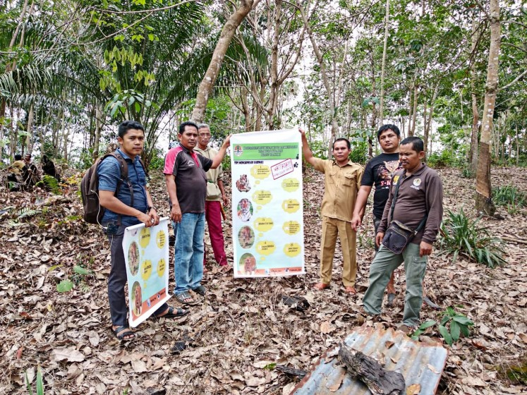 Members of a Quick Response team dispatched by the Riau Natural Resources Conservation Agency examine the suspected Sumatran tiger prints on Tuesday.