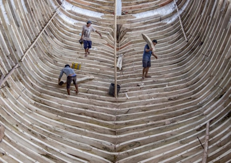 This picture taken on July 7, 2018 shows shipbuilders working on a traditional Pinisi boat in Tana Beru, on South Sulawesi island.