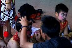 A boy has makeup put on before the performance. JP/Maksum Nur Fauzan