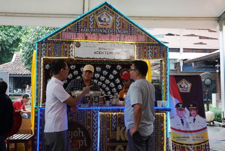 Central Aceh Regent Shabela Abubakar (second left) engages with visitors at the festival's Central Aceh booth.