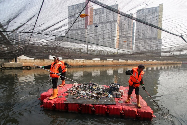 City workers clean the Sentiong River under a giant nylon net in Central Jakarta on July 21. The city administration covered the river in an attempt to ward off the smell ahead of the 18th Asian Games in August.