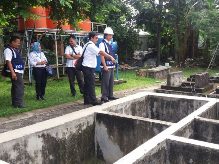 Officials from the city administration and city-owned wastewater management firm PD PAL Jaya inspect a communal wastewater treatment site in Malakasari, East Jakarta, in 2017.