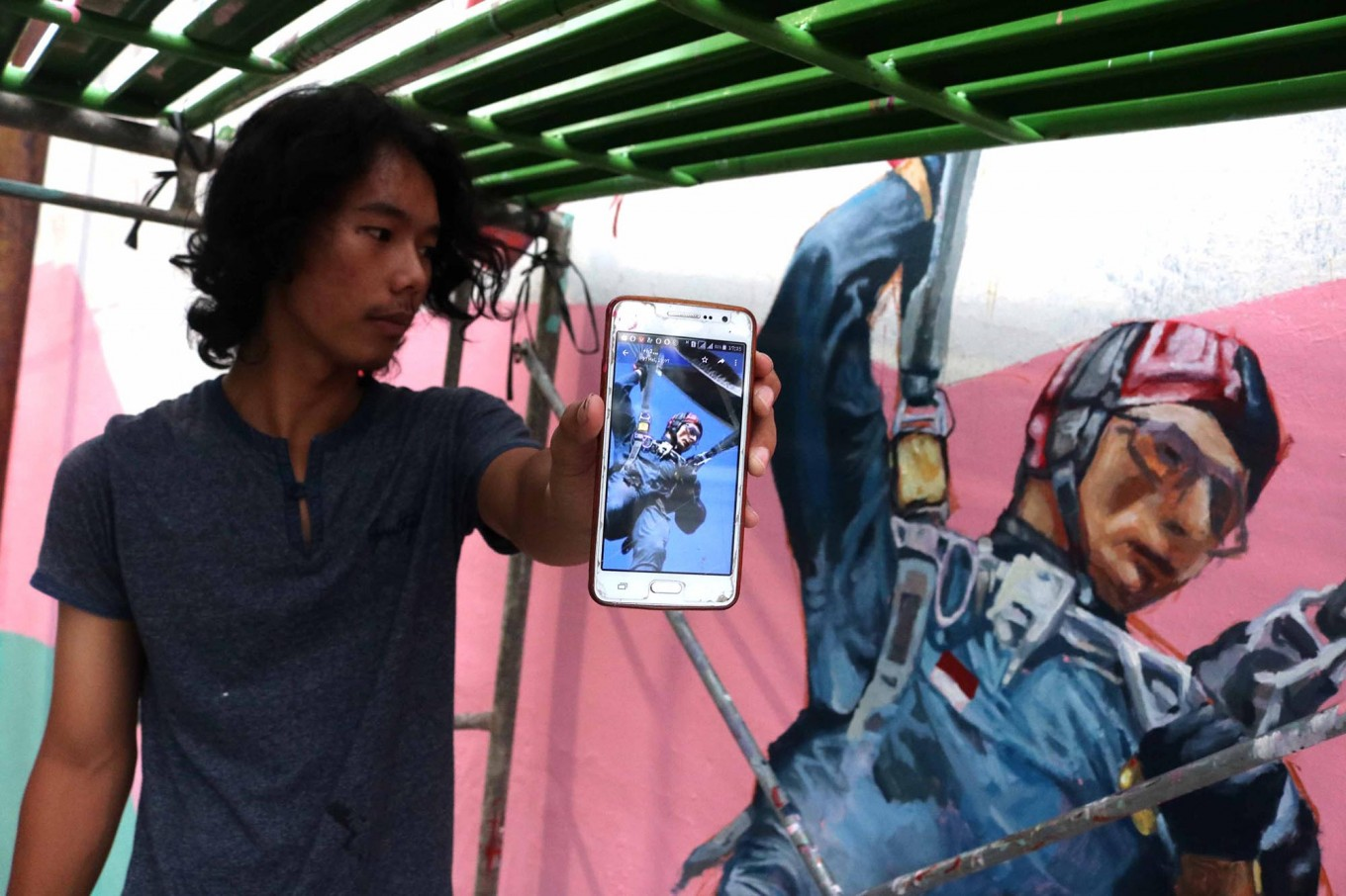 One of the artists shows a picture of his work on his phone. JP/Maksum Nur Fauzan