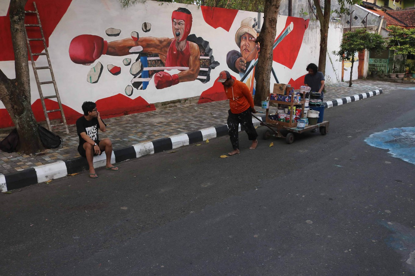 Artists pull a cart loaded with paint to continue working on their murals. JP/Maksum Nur Fauzan