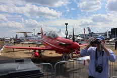 Closer look: A visitor of the Farnborough airshow uses binoculars to check out civilian and military planes. JP/ R. Berto Wedhatama