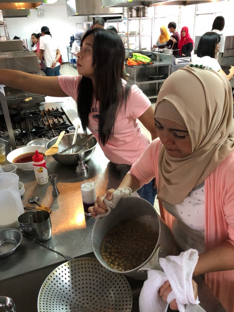 Indonesian migrant workers learn how to make bubble tea.