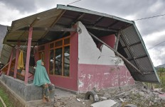 A woman sits in front of her partially collapsed house in Sembalun Bumbung village, Sembalun district, East Lombok. Antara/Ahmad Subaidi