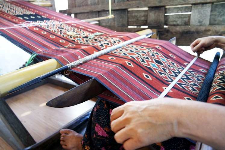 Colorful: A weaver works on a piece of Toraja fabric in South Sulawesi.