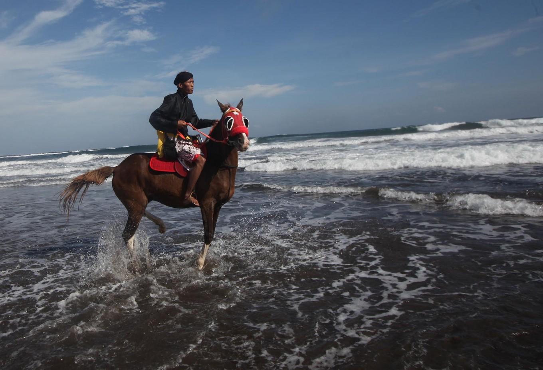 A man rides his horse along the beach. JP/Boy T. Harjanto