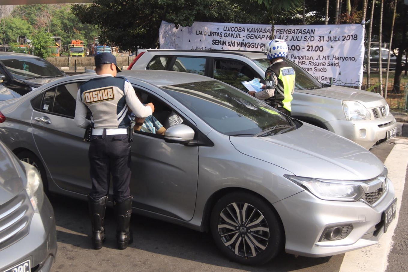 On alert: An officer of the Jakarta Transportation Agency speaks to a driver in Tomang, West Jakarta, on Monday, July 2, 2018. The capital's transportation agencies have started a one-month trial of an extended odd-even traffic policy that is expected to tackle road congestion ahead of the Asian Games in August. JP/Wendra Ajistyatama
