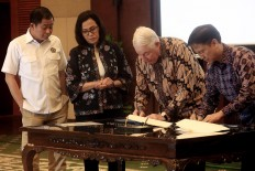 Bigger share: Freeport-McMoRan Copper & Gold Inc. CEO Richard Adkerson (second right) and PT Indonesia Asahan Aluminium (Inalum) president director Budi Gunadi Sadikin (right) sign a divestment agreement, witnessed by Energy and Mineral Resources Minister Ignasius Jonan (left) and Finance Minister Sri Mulyani in Jakartra on Thursday, July 12, 2018. The government, through Inalum, will have a 51 percent stake in PT Freeport Indonesia following the agreement. JP/Dhoni Setiawan