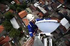 A technician carries out maintenance on a 4G base transceiver station (BTS) in Bendungan Hilir, Central Jakarta, on Friday, July 13, 2018. Publicly listed telecommunications company XL Axiata operates 2,700 4G LTE BTS across Jakarta. JP/ Dhoni Setiawan