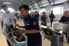 System maintenance: Officials from commuter train operator Kereta Commuter Indonesia (KCI) upgrade an electronic gate at Palmerah Station in Central Jakarta on Monday, July 23, 2018. KCI began maintenance work and upgraded its e-ticketing system on Sunday. JP/Dhoni Setiawan