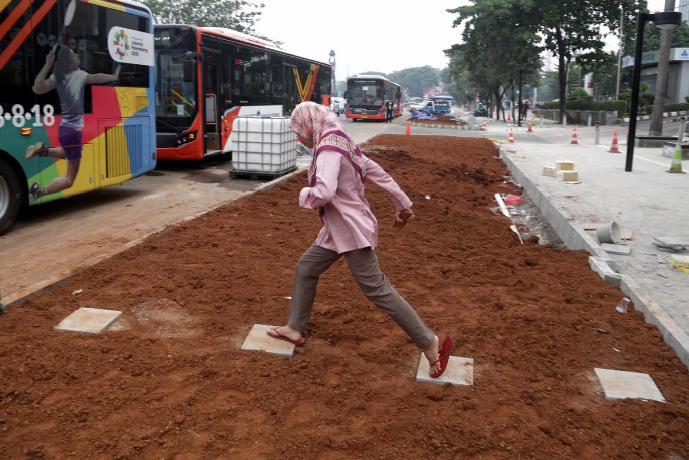 A commuter hops across a footpath to get to a bus in Sudirman, Central Jakarta, on Tuesday, July 24, 2018. In the city administration's new sidewalk design, a 2.5-meter green space will separate the sidewalk and bus stops. JP/Wendra Ajistyatama