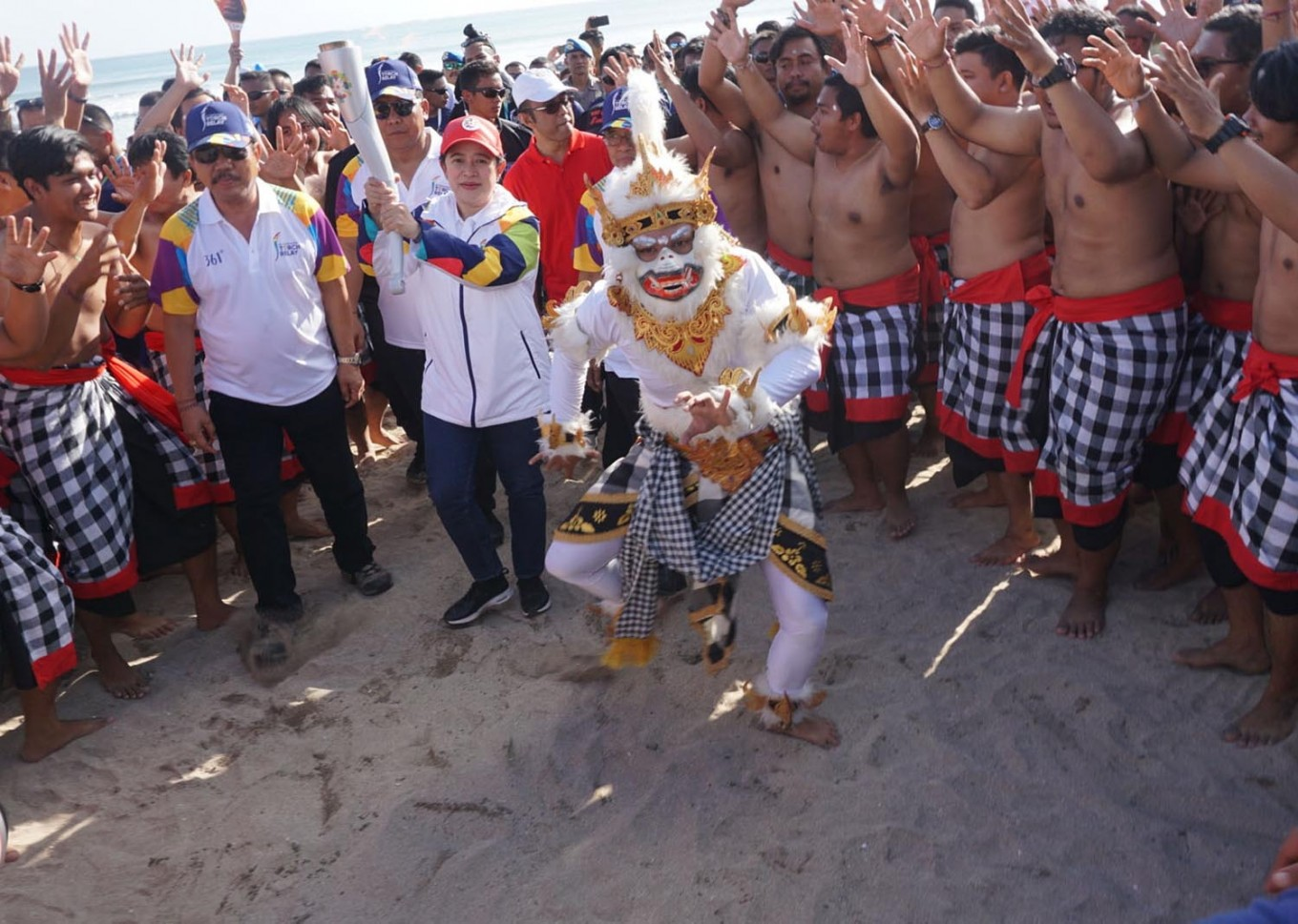 Welcome to Bali: Coordinating Human Development and Culture Minister Puan Maharani carries the Asian Games torch at Kuta Beach, Bali, as part of the Asian Games torch relay on Monday, July 23, 2018. The torch was welcomed by kecak dancers and will be carried around the resort island for two days before being taken to West Nusa Tenggara on Wednesday. JP/ Ni Komang Erviani