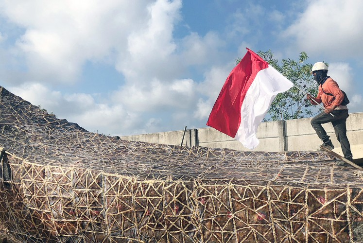 For the country: A worker scales the statue's 1,500th and final piece while carrying the Indonesian flag.