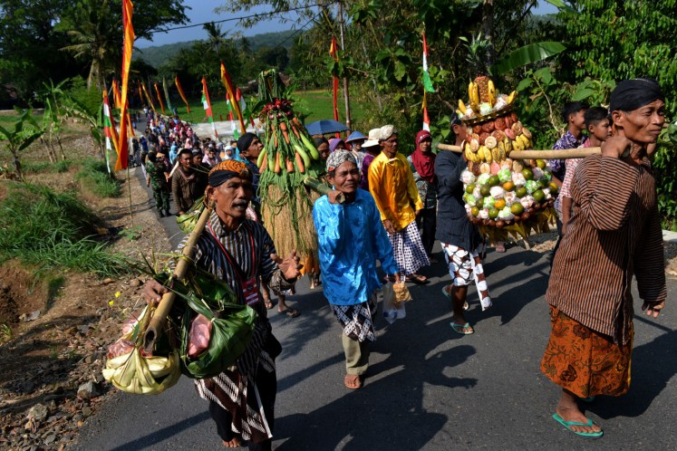Residents carry offerings as they walk to the forest.