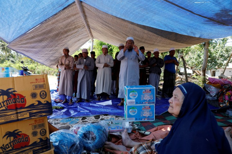 Villagers hold evening prayer inside a temporary shelter after an earthquake hit Lombok island in Pamenang, Indonesia August 6, 2018.