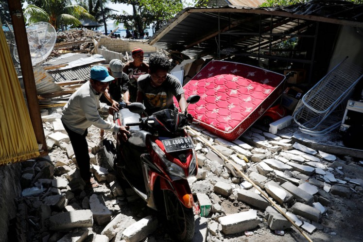 Villagers push a motorcycle along ruins after an earthquake hit Lombok island in Pamenang, Indonesia August 6, 2018. REUTERS/Beawiharta
