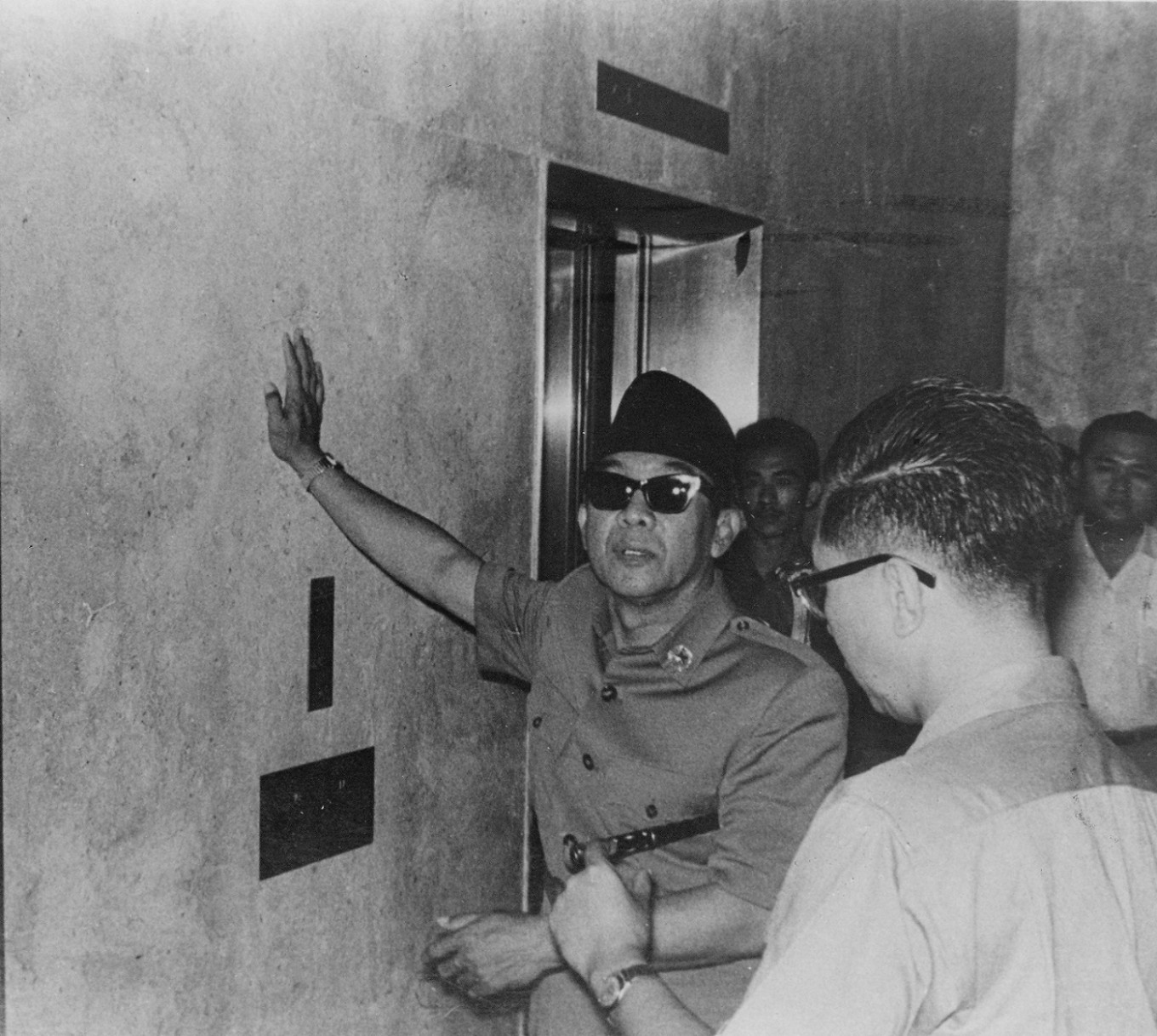 President Sukarno stands in front of the first elevator in Indonesia.