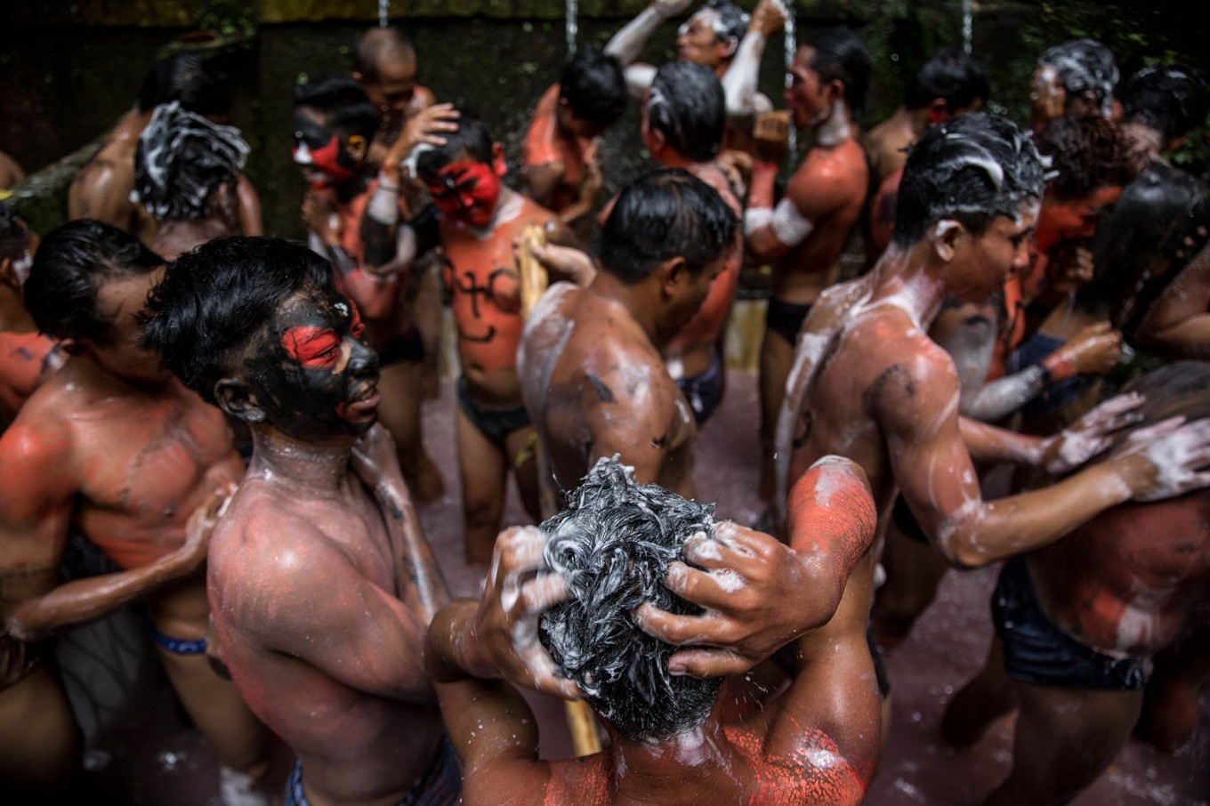 Young people wash their hair and bodies to clean off paint after the Ngarebeg ritual. JP/Agung Parameswara