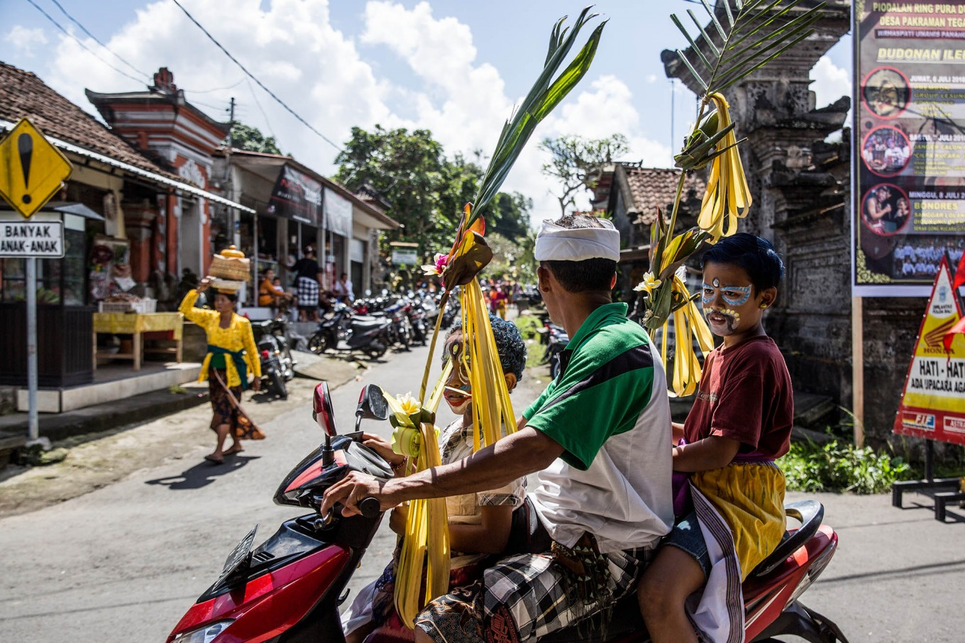 A Balinese man rides a motorcycle with his children to join the Ngerebeg ritual. JP/Agung Parameswara