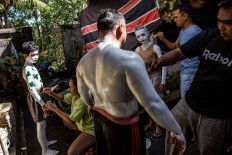 Balinese boys paint their bodies prior to the Ngerebeg ritual in Tegalalang village, Gianyar district, Bali. JP/Agung Parameswara