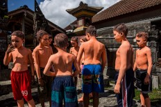 Boys color their bodies before joining the Ngerebeg ritual in Tegalalang village, Gianyar district, Bali. JP/Agung Parameswara