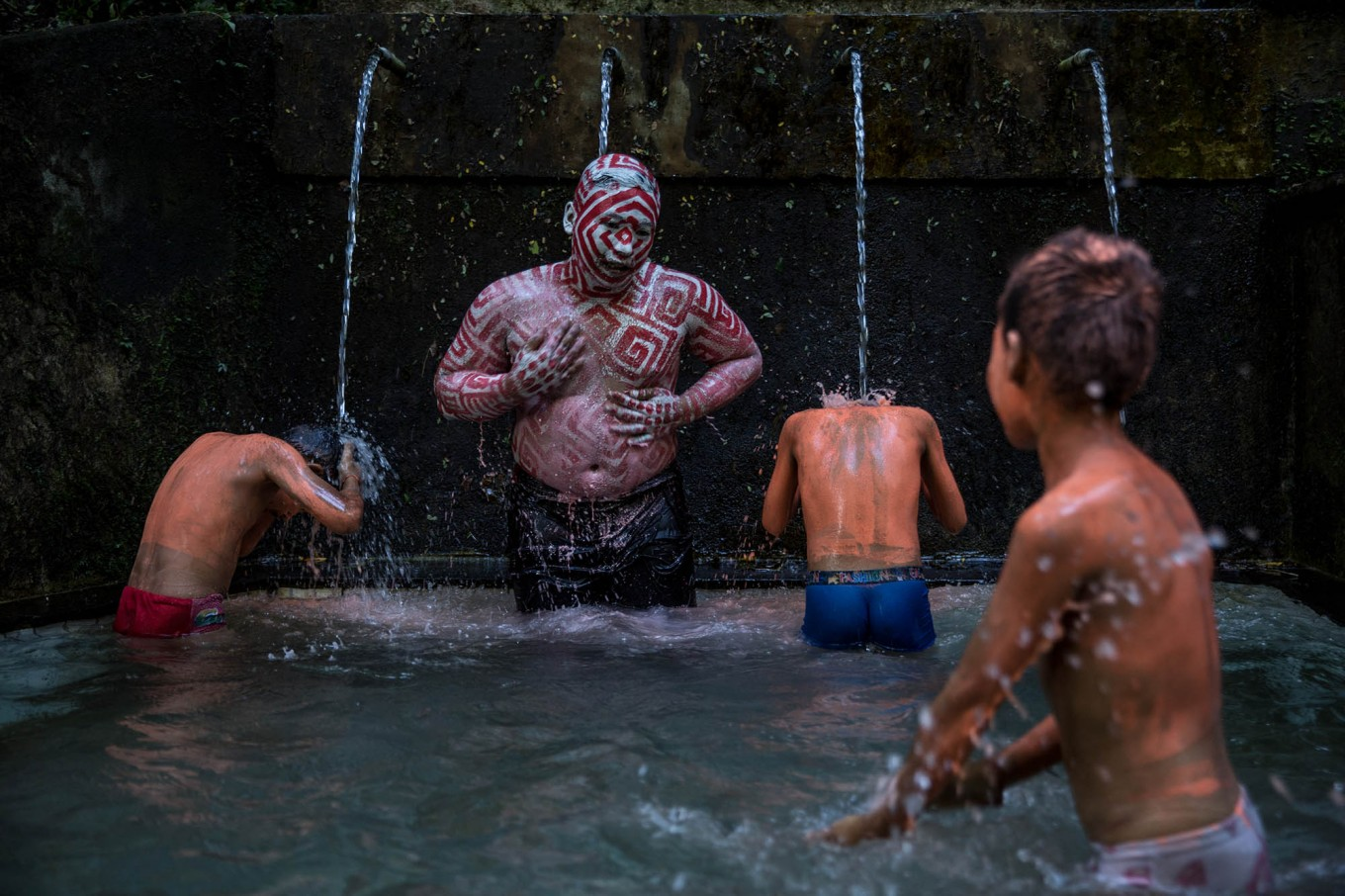 After finishing the ritual, the villagers wash the paint off their bodies at a spring. JP/Agung Parameswara