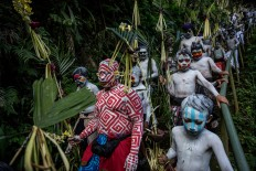 Young villagers walk around their village with their bodies painted. JP/Agung Parameswara