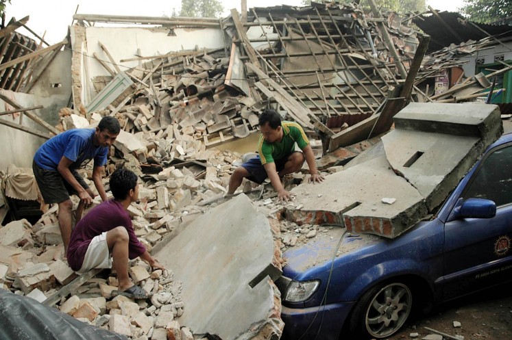 Residents try to remove concrete rubble from on top of their car after a strong earthquake in Yogyakarta on May 27, 2006.