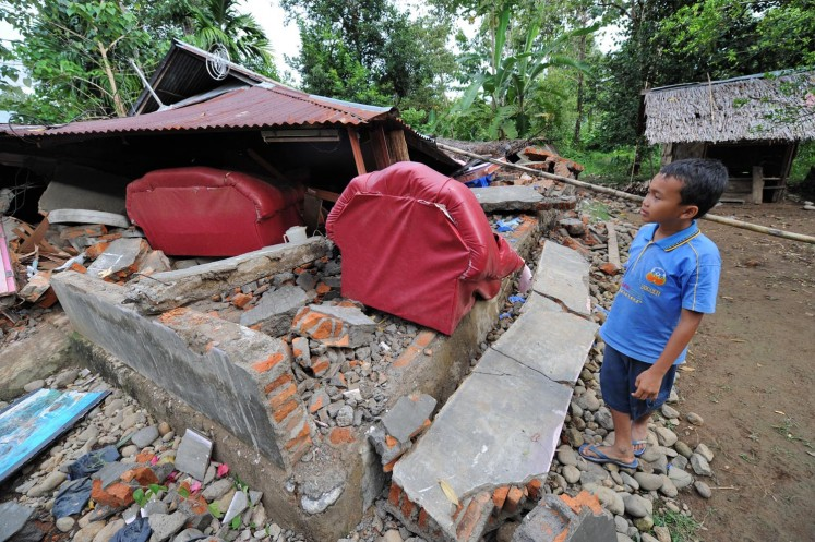 A boy looks at his flattened home after a 7.6-magnitude earthquake hit Padang, Sumatra, in October 2009.