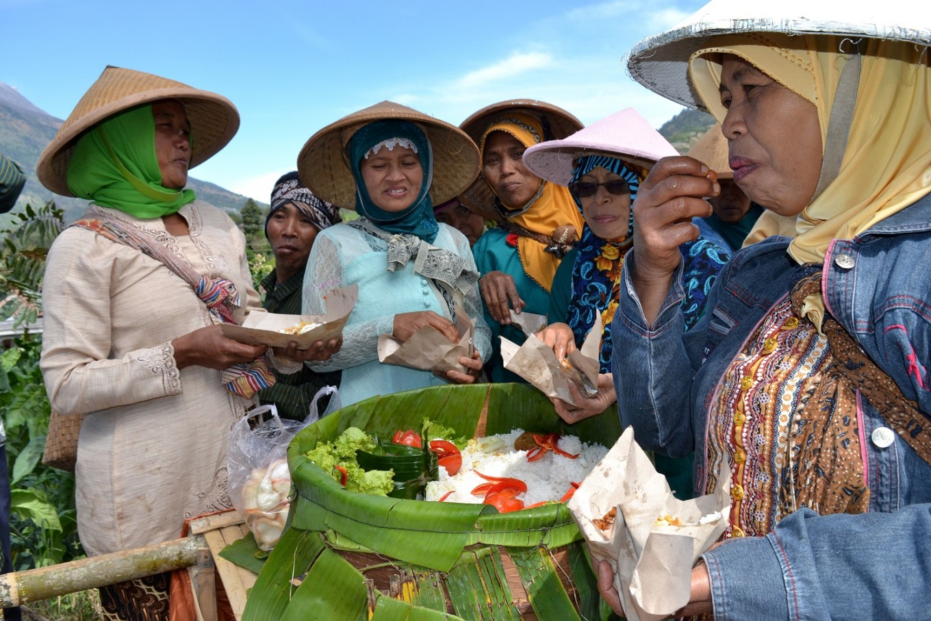 Villagers enjoy 'tumpeng' (yellow rice cones) during the Tungguk Tembakau Festival.
