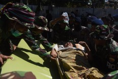 Military personnel lift an injured victim to a health tent at Tanjung Hospital in North Lombok on Tuesday Aug. 7, 2018. Antara/Zabur Karuru