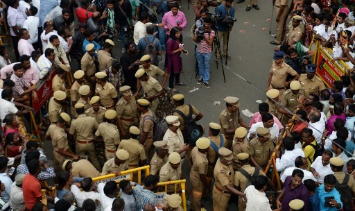 Indian policemen stand guard as supporters of the Dravida Munnetra Kazhagam party gather in front of the hospital where President M. Karunanidhi died, in Chennai on August 7, 2018. Thousands of people desanded into mourning on August 7 in southern India after the death of revered 94-year-old political leader Muthuvel Karunanidhi.