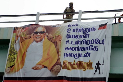 An Indian policeman stands next to a banner with the picture of Dravida Munnetra Kazhagam (DMK) party President M. Karunanidhi at the hospital where he is being treated, in Chennai on August 6, 2018.