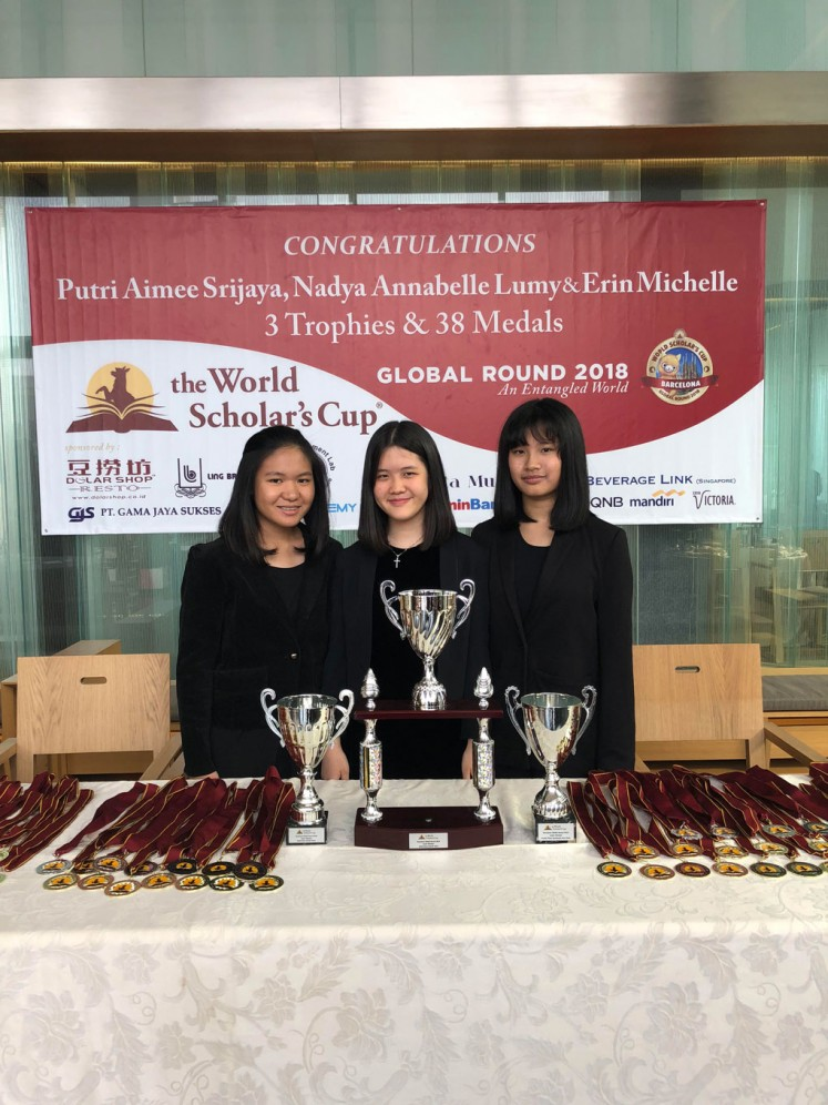 Nadya Annabelle Lumy (left), Putri Aimee Srijaya (center) and Erin Michelle pose for a photo with the three trophies and 38 medals they won at the World Scholar's Cup in Barcelona.