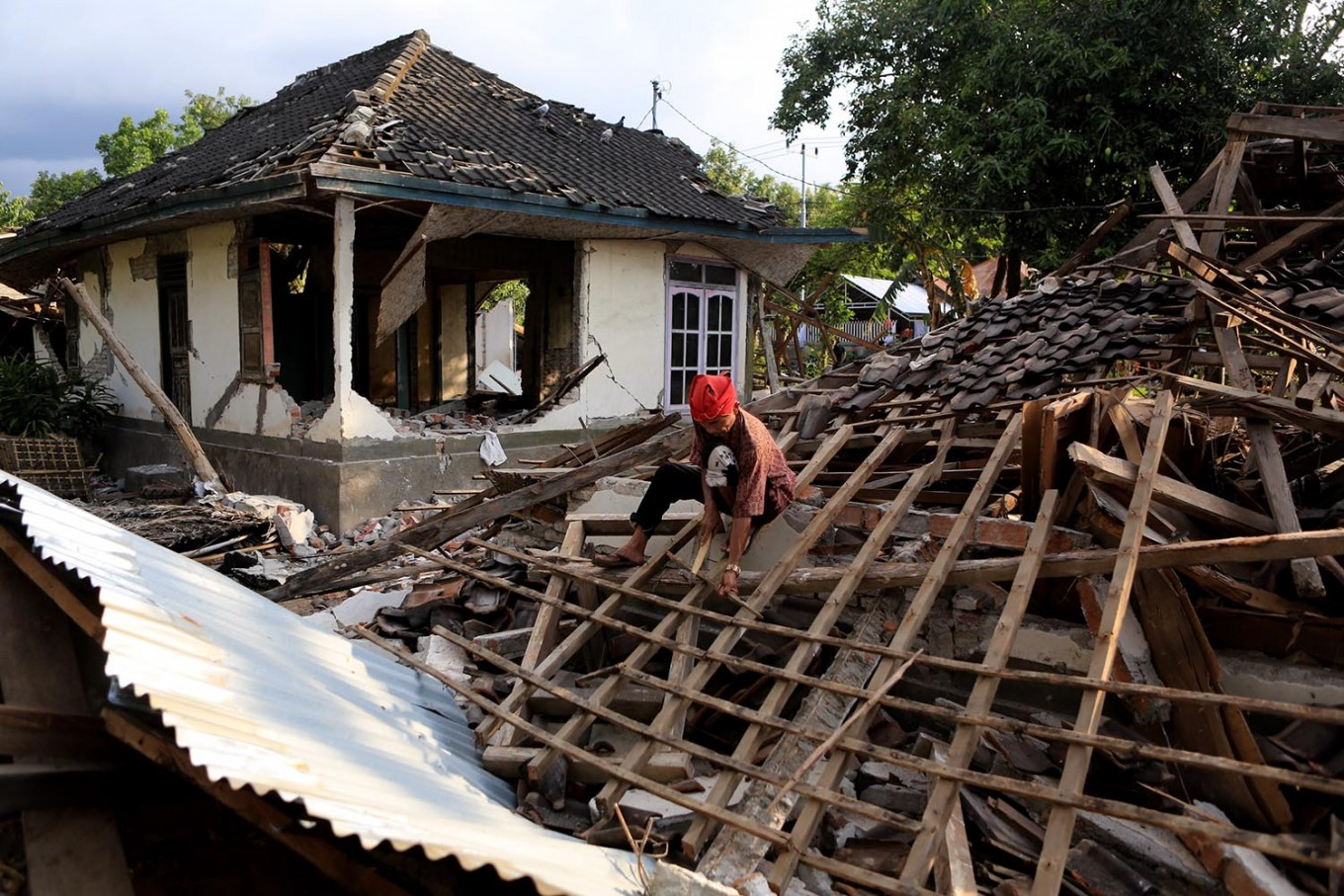 A villager looks for personal belongings after his home was destroyed in an earthquake in Bentek village, Gangga district, North Lombok, on Wednesday Aug. 8, 2018. JP/Seto Wardhana